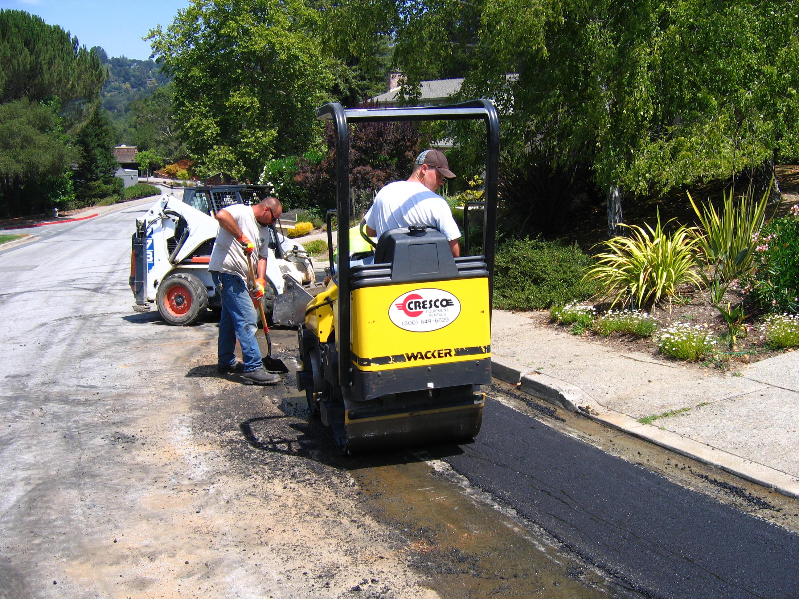Two men doing road repairs on a residential street.
